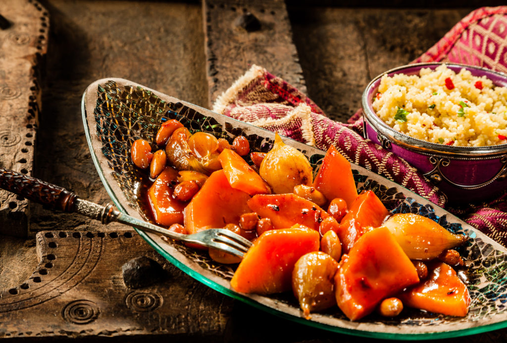 Still Life of Traditional Tajine Vegetable Dish Made with Bright Orange Vegetables in Sauce and Served in Long Narrow Modern Dish with Fork on Rustic Wooden Table with Couscous